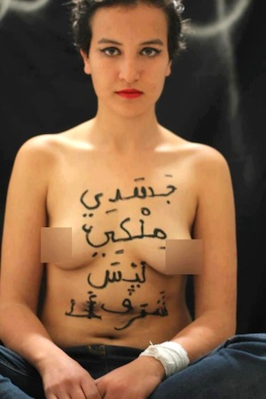 """Topless Tunisian feminist Amina with the phrase """"My body is mine, not somebody's honour"""" inscribed across her breasts and stomach in Arabic"""