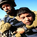 Israeli soldier arrests palestinian child