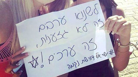 """Two Israeli Jewish girls with a sign in Hebrew that reads """"Hating Arabs is not racism, it's values"""""""