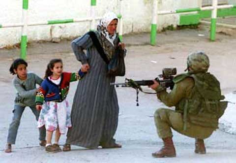 Israeli soldier points his gun at a Palestinian woman and her children