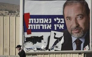"""An ultra-Orthodox Jewish man passes an election campaign poster for the leader of Israel's right-wing Yisrael Beiteinu Party, Avigdor Lieberman, in Jerusalem, Thursday Feb. 5, 2009. General elections in Israel are scheduled for Feb. 10, 2009, and pre-election polls show Likud Party leader Benjamin Netanyahu with a lead over Foreign Minister and Kadima Party leader Tzipi Livni. The campaign slogan on the poster reads """"Without loyalty, there is no citizenship."""" (AP Photo/Peter Dejong)"""