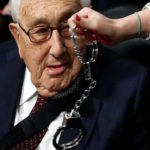 Henry Kissinger looking at handcuffs